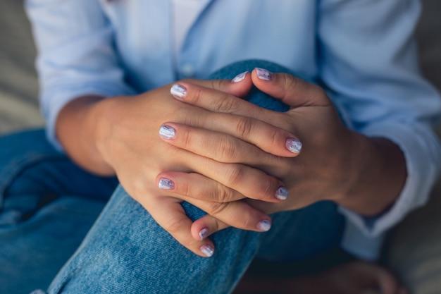 정사각형 손톱에 은색 장식 조각이있는 분홍색 매니큐어
