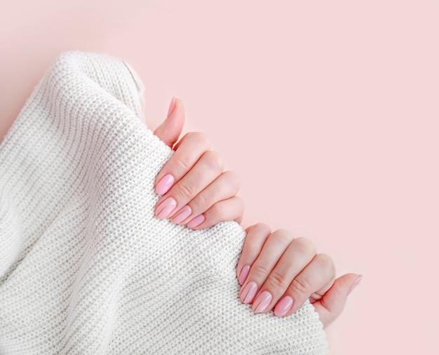 Розовый маникюр женские руки держат белое покрывало на розовом фоне оттенок нюдового гель-лака