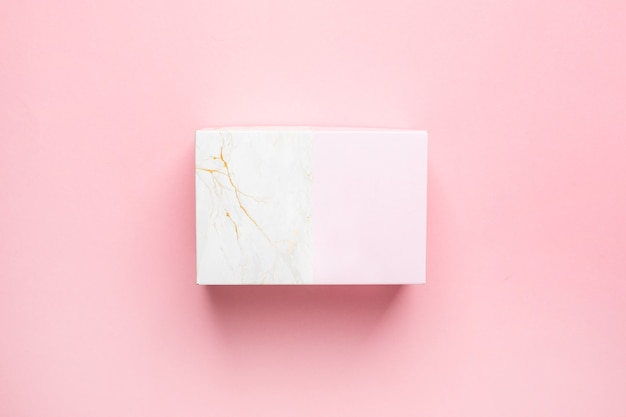 Pink and marble gift present box isolated on pastel pink background top view