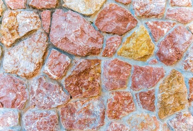 ピンクの大理石の石の壁のテクスチャ。クローズアップ表面グランジ石のテクスチャ、石細工の岩
