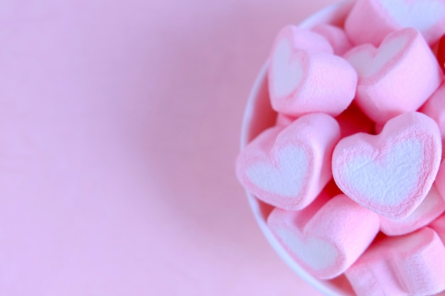 Pink marshmallow background, heart marshmallow in white cup, valentine background