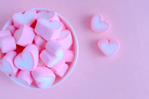 Pink marshmallow background, heart marshmallow in white cup,