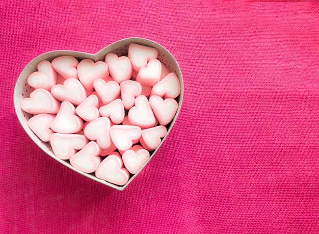 Pink marshmallow in a gift box in form of heart on pink canvas
