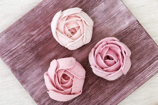 Розовый зефир цветы розы на старой деревянной доске. красиво оформленный десерт. низкокалорийная сладость. вид сверху.