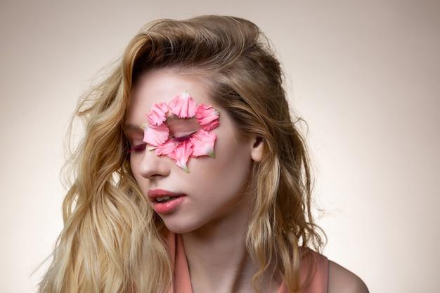 ピンクのマスカラ。ピンクのマスカラがポーズをとっている間目を閉じているブロンドの髪の魅力的な若いモデル