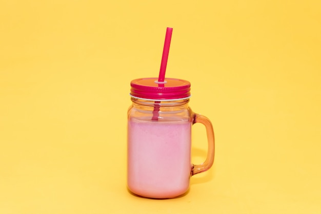 Pink mason mug with cocktail on yellow background. seashells