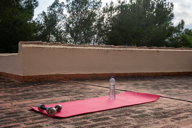 Розовый коврик на террасе на полу для гантелей для йоги и бутылки с водой