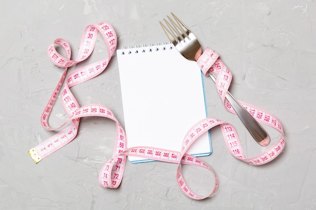 Pink measure tape, open notebook and fork