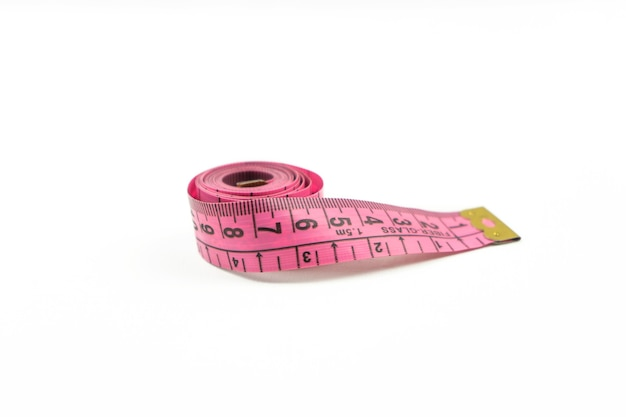 A pink measuring tape lies on a white table