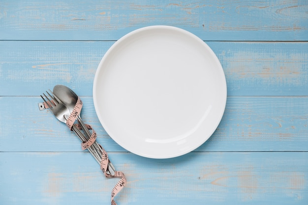 Pink measuring tape wrapped around fork and spoon with white dish