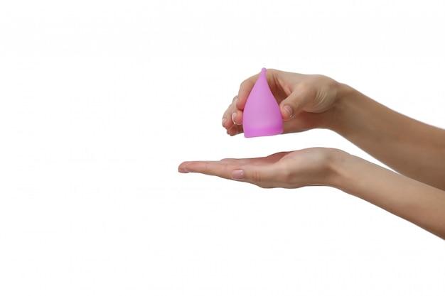 ピンクの月経カップ。白い背景の上に月経カップを持つ女性の手のクローズアップ。女性の健康概念、廃棄物ゼロの選択肢