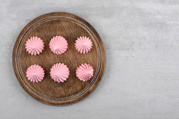 Pink meringue on a board, on the marble table.