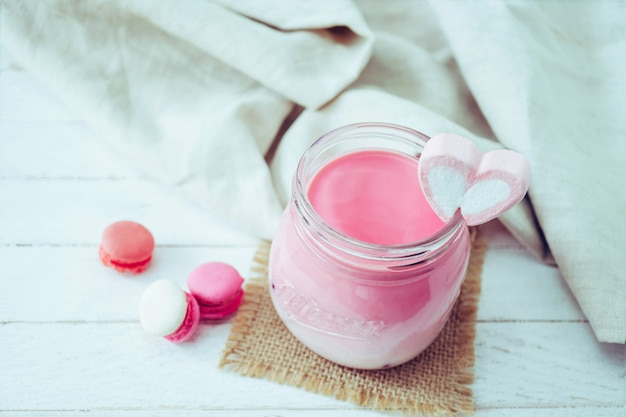 Pink milkshake with heart shape marshmallows on wood background
