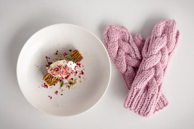 핑크 벙어리 장갑과 흰색 나무 테이블에 케이크. 크리스마스와 새 해 배경