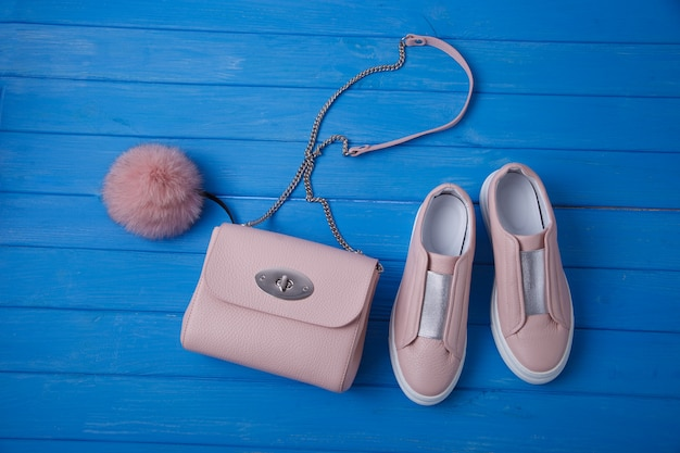 Pink moccasins and clutch bag with fur bubo on blue wooden wall
