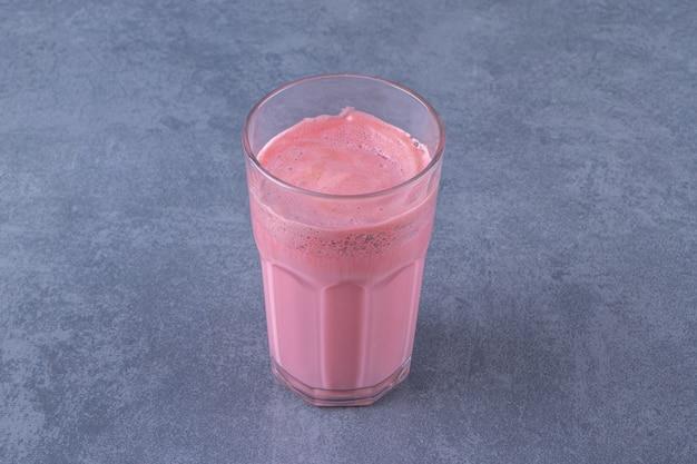 大理石のテーブルの上に、グラスにミルクを入れたピンクのモカラテ