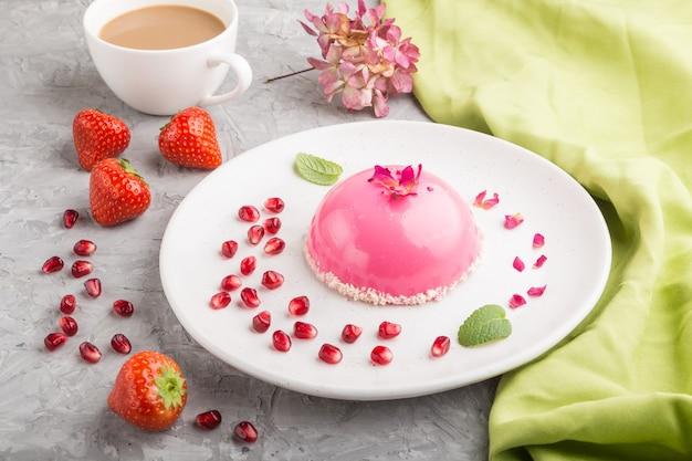 Розовый муссовый торт с клубникой и чашкой кофе на серой бетонной поверхности и зеленой ткани