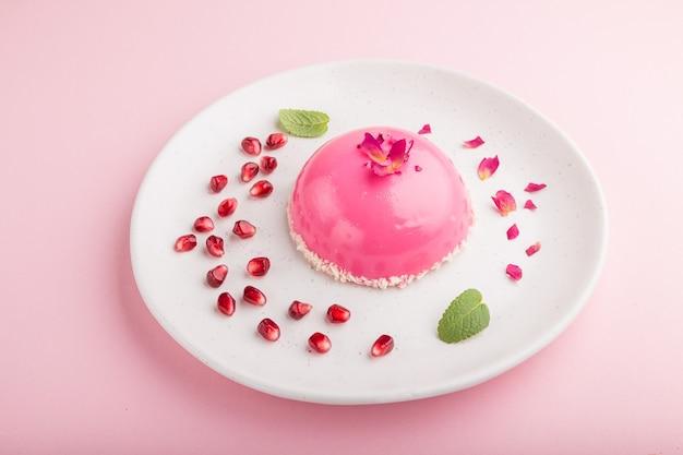 Розовый муссовый торт с клубникой на пастельно-розовой поверхности