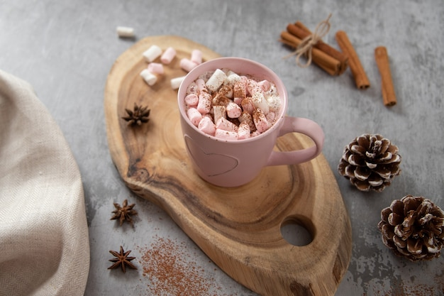 Pink mug of cocoa with white-pink marshmallows, cinnamon sticks and star anises