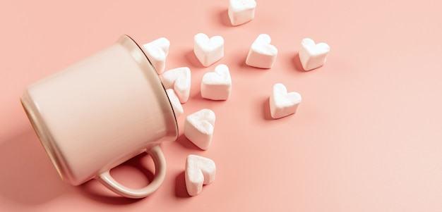 A pink mug lies on its side against a pink surface, light pink marshmallows sprinkled from it in the form of hearts