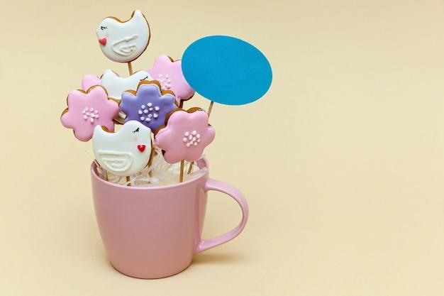 베이지색 배경에 꼬치에 쿠키와 핑크 머그. 음식 개념입니다. 텍스트 및 디자인을 위한 장소가 있는 사진.