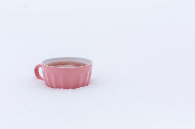 A pink mug with a drink is standing in the snow on a street in winter