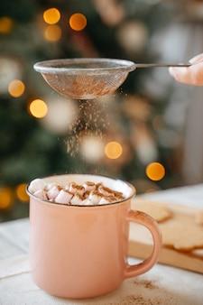 뜨거운 크리스마스 코코아 마시멜로가 든 핑크 머그에 체에서 매운 계피를 뿌렸습니다. 새 해의 개념입니다.