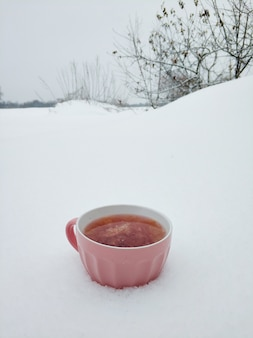 A pink mug with hot raspberry tea on the background of a snowy winter field. tea with jam warms in cold winter.