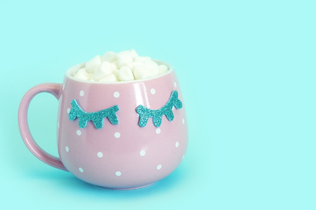 Pink mug with white polka dots with blue closed eyes with coffee and marshmallows. shiny eyelashes. blue background.