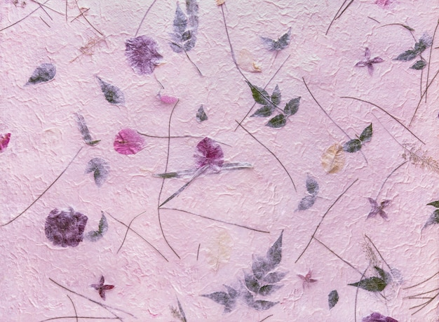 Pink mulberry paper with the texture of flowers and foliage is used as a background.