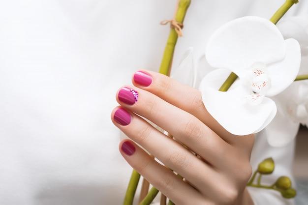 Розовый дизайн ногтей. женская рука с блеском маникюра.