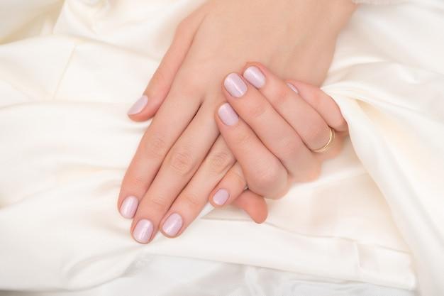 핑크 네일 디자인. 반짝이 매니큐어와 여성의 손입니다.