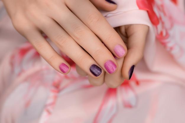 ピンクのネイルデザイン。ピンクの手入れの行き届いた女性の手