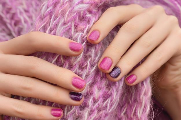 ピンクのネイルデザイン。ピンクの背景に手入れの行き届いた女性の手。