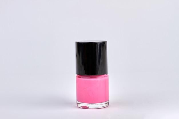 白で隔離のピンクのマニキュアボトル。ピンクのマニキュアをクローズアップ。