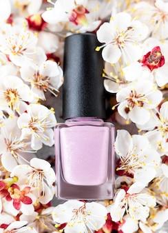 Розовая бутылка лака для ногтей на фоне цветущей вишни весной. розовая бутылка лака для ногтей на цветочном фоне.
