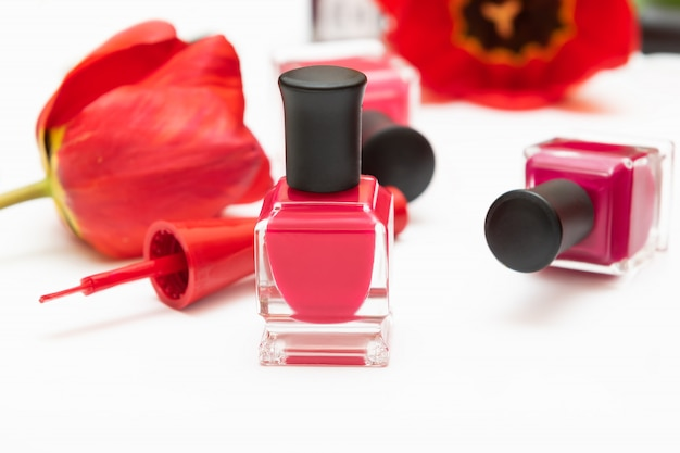 Pink nail polish bottles and tulip flowers on white background