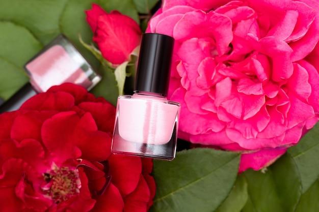 粉红色的指甲油瓶子上盛开着粉红色和红色的玫瑰。粉红色的指甲油瓶子在红色的花的背景。