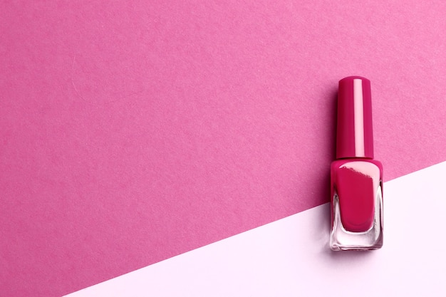 Pink nail polish on pink background with place for text.