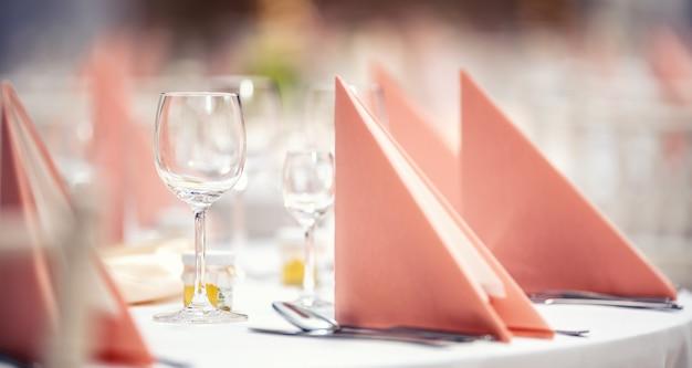 분홍색 냅킨은 옆에 유리 제품과 칼 붙이와 함께 축제 테이블에 접혀 있습니다.