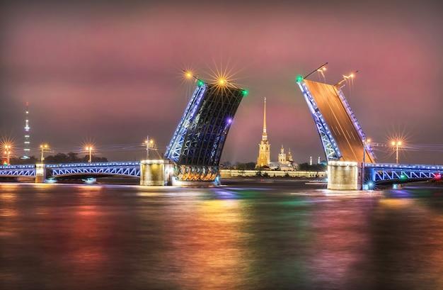 Розовое ночное небо над открывшимся дворцовым мостом, через который видна петропавловская крепость.