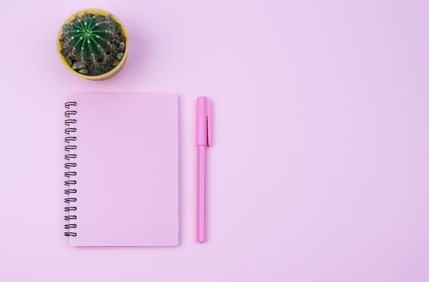 Розовый блокнот и розовая ручка на розовом фоне