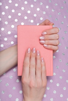 Pink notebook in female hands