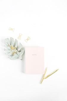 핑크 노트북, 황금 펜 및 클립, 흰색 바탕에 monstera 팜 리프 장식. 평면 위치, 최고보기 홈 오피스 데스크 개념.