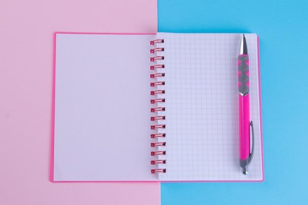 明るいマルチカラーの背景にピンクのペンでピンクのノート。