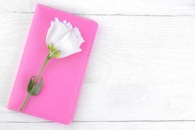 흰색 나무 탁자 위에 흰색 꽃 유스토마가 있는 분홍색 노트북