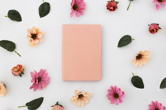 Pink notebook with pattern of flowers around on white background
