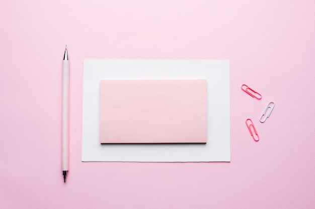 Pink notepad for text on pastel pink background.