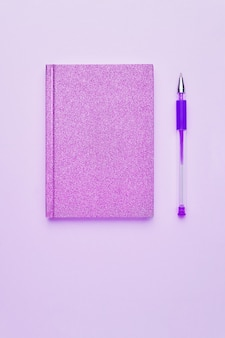 Розовый блокнот с ручкой на пастельно-розовом фоне на неоновом свете обратно в школу