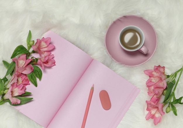 Pink notes paper on white furry background with flowers and cup of coffee